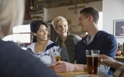 Friends talking and drinking beer at brewery